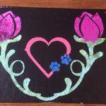 A black background with 2 green stems on either side with pink roses on top. In the middle a salmon colored heart with blue pawprints